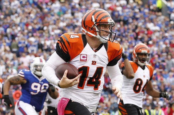 Oct 13, 2013; Orchard Park, NY, USA; Cincinnati Bengals quarterback Andy Dalton (14) runs the ball against Buffalo Bills defensive end Alan Branch (90) during the second half at Ralph Wilson Stadium. Bengals beat the Bills 27-24 in overtime. Mandatory Credit: Kevin Hoffman-USA TODAY Sports