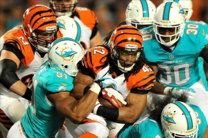 Oct 31, 2013; Miami Gardens, FL, USA; Cincinnati Bengals running back BenJarvus Green-Ellis (42) is tackled by Miami Dolphins defensive end Cameron Wake (91) during the first quarter at Sun Life Stadium. Mandatory Credit: Steve Mitchell-USA TODAY Sports