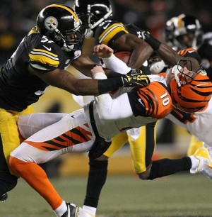 Dec 15, 2013; Pittsburgh, PA, USA; Pittsburgh Steelers linebacker Terence Garvin (57) tackles Cincinnati Bengals punter Kevin Huber (10) during the first quarter at Heinz Field. Mandatory Credit: Jason Bridge-USA TODAY Sports