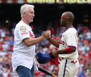 Jun 14, 2014; Philadelphia, PA, USA; Philadelphia Phillies shortstop Jimmy Rollins (11) hits a single to right in the fifth inning to become the all time franchise hit leader and is congratulated by former record holder Mike Schmidt during a game against the Chicago Cubs at Citizens Bank Park. Mandatory Credit: Bill Streicher-USA TODAY Sports