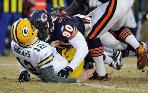 Jan 23, 2011; Chicago, IL, USA; Green Bay Packers quarterback Aaron Rodgers (12) is hit by Chicago Bears defensive end Julius Peppers (90) during the fourth quarter of the 2011 NFC championship game at Soldier Field. Peppers was flagged for a penalty on the play for helmet-to-helmet contact. Mandatory Credit: Rob Grabowski-US PRESSWIRE