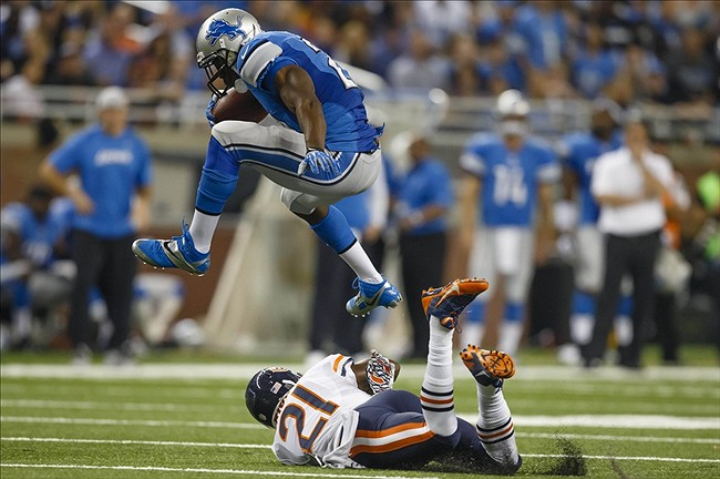 Sep 29, 2013; Detroit, MI, USA; Detroit Lions running back Reggie Bush (21) leaps over Chicago Bears strong safety Major Wright (21) on his way to a thirty seven yard touchdown run in the second quarter at Ford Field. Mandatory Credit: Rick Osentoski-USA TODAY Sports