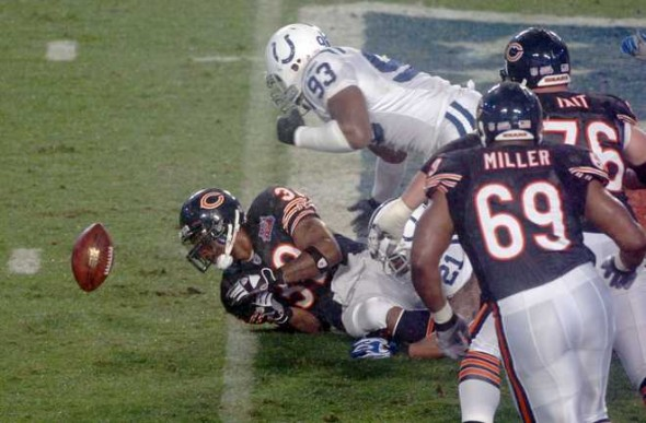 Indianapolis Colts defensive end Dwight Freeney (93) and Chicago Bears running back Cedric Benson (32) reach for Benson's fumble during the first quarter of Super Bowl XLI on Sunday, Feb. 4, 2007 at Dolphin Stadium in Miami Gardens. WALTER MICHOT / STAFF PHOTO