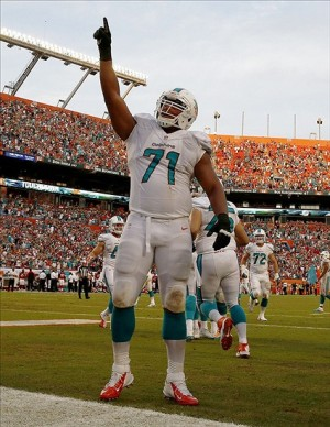 Sep 22, 2013; Miami Gardens, FL, USA; Miami Dolphins tackle Jonathan Martin (71) reacts after a touchdown by tight end Dion Sims (not pictured) in the fourth quarter against the Atlanta Falcons at Sun Life Stadium. Miami won 27-23. Mandatory Credit: Robert Mayer-USA TODAY Sports