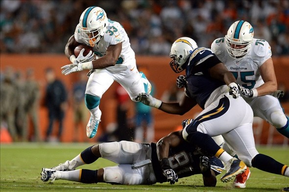 Nov 17, 2013; Miami Gardens, FL, USA; Miami Dolphins running back Daniel Thomas (33) jumps over San Diego Chargers defensive end Kendall Reyes (91) during the second half at Sun Life Stadium. The Dolphins won the game 20-16. Mandatory Credit: Joe Camporeale-USA TODAY Sports