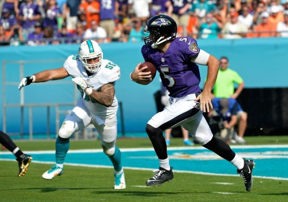 Dec 7, 2014; Miami Gardens, FL, USA; Baltimore Ravens quarterback Joe Flacco (5) runs past Miami Dolphins outside linebacker Koa Misi (55) during the first half at Sun Life Stadium. Mandatory Credit: Steve Mitchell-USA TODAY Sports