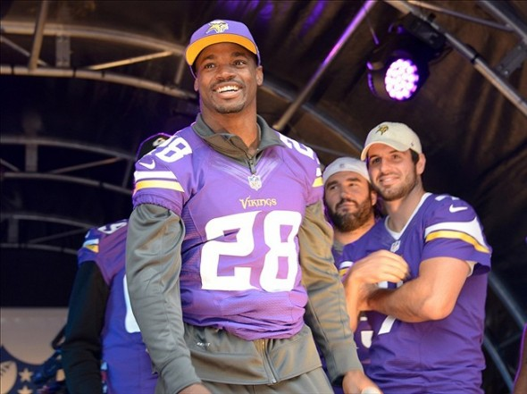Sep 28, 2013; London, UNITED KINGDOM; Minnesota Vikings running back Adrian Peterson (28) flanked by quarterback Christian Ponder (7) at the NFL on Regent Street block party in advance of the NFL International Series game between the Pittsburgh Steelers and the Minnesota Vikings. Mandatory Credit: Kirby Lee-USA TODAY Sports