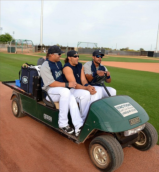 Mar 21, 2013; Peoria, AZ, USA; Seattle Mariners center fielder Franklin Gutierrez (right) drives a golf cart with left fielder Michael Morse (center) and first baseman Kendrys Morales (left) squeezed into the front seat after batting practice before a game against the Chicago Cubs at Peoria Sports Complex. Mandatory Credit: Jake Roth-USA TODAY Sports