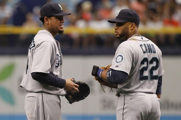 Jun 8, 2014; St. Petersburg, FL, USA; Seattle Mariners starting pitcher Felix Hernandez (34) talks to second baseman Robinson Cano (22) on the field against the Tampa Bay Rays during the second inning at Tropicana Field. Mandatory Credit: Kim Klement-USA TODAY Sports