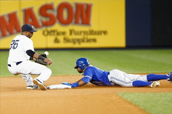 Aug 21, 2013; Bronx, NY, USA; New York Yankees shortstop Eduardo Nunez (26) bobbles the ball at second base as Toronto Blue Jays left fielder Rajai Davis (11) steals the base during the sixth inning at Yankee Stadium. Mandatory Credit: Debby Wong-USA TODAY Sports