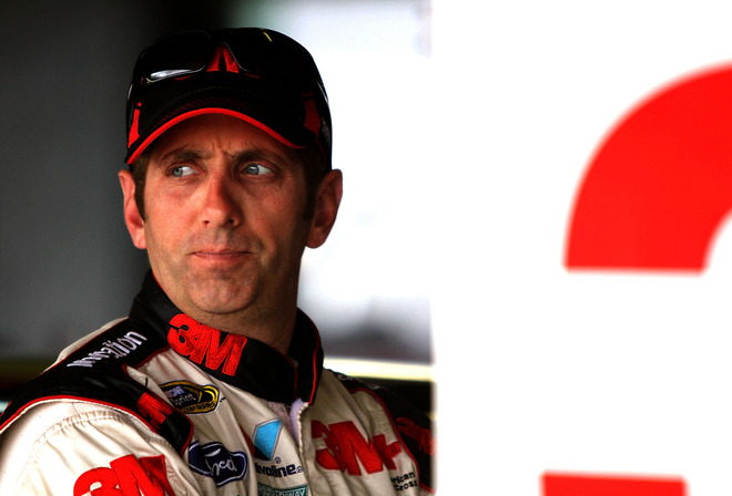 : Greg Biffle, driver of the #16 3M Novec Ford, stands in the garage prior to practice for the NASCAR Sprint Cup Series Ford 400 at Homestead-Miami Speedway on November 18, 2011 in Homestead, Florida. (Photo by Jerry Markland/Getty Images for NASCAR)