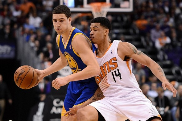 Dec 15, 2013; Phoenix, AZ, USA; Golden State Warriors guard Klay Thompson (11) dribbles the ball around defender Phoenix Suns guard Gerald Green (14) in the first half at US Airways Center. Mandatory Credit: Jennifer Stewart-USA TODAY Sports