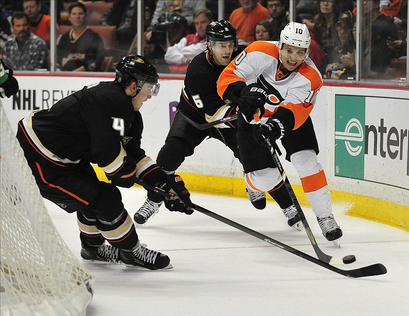 January 30, 2014; Anaheim, CA, USA; Philadelphia Flyers center Brayden Schenn (10) moves the puck against the defense of Anaheim Ducks defenseman Cam Fowler (4) and defenseman Ben Lovejoy (6) during the third period at Honda Center. Mandatory Credit: Gary A. Vasquez-USA TODAY Sports
