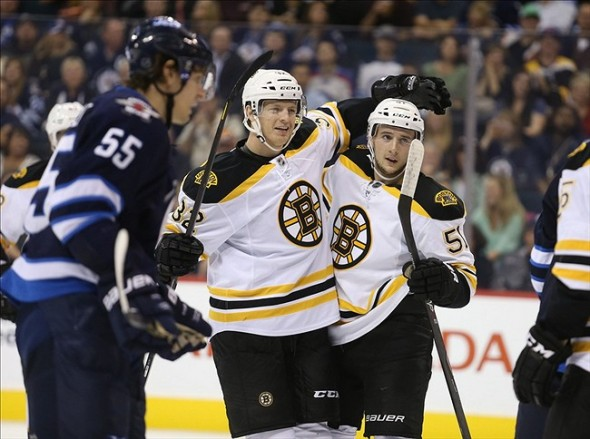 Sep 26, 2013; Winnipeg, Manitoba, CAN; Boston Bruins forward Matt Fraser (25) comes to celebrate his goal with teammates Nick Johnson (32) and forward Ryan Spooner (51) during the third period at MTS Centre. Bruins win 3-2. Mandatory Credit: Bruce Fedyck-USA TODAY Sports