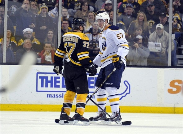 Dec 21, 2013; Boston, MA, USA; Boston Bruins center Patrice Bergeron (37) and Buffalo Sabres defenseman Tyler Myers (57) exchange words during the second period at TD Banknorth Garden. Mandatory Credit: Bob DeChiara-USA TODAY Sports