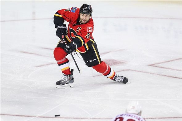 Jan 22, 2014; Calgary, Alberta, CAN; Calgary Flames defenseman Mark Giordano (5) passes the puck against the Phoenix Coyotes during the third period at Scotiabank Saddledome. Calgary Flames won 3-2. Mandatory Credit: Sergei Belski-USA TODAY Sports