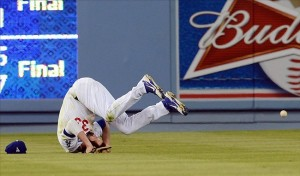 Scott Van Slyke rolls over trying to catch the ball in left field. Photo: Jayne Kamin-Oncea-USA TODAY Sports