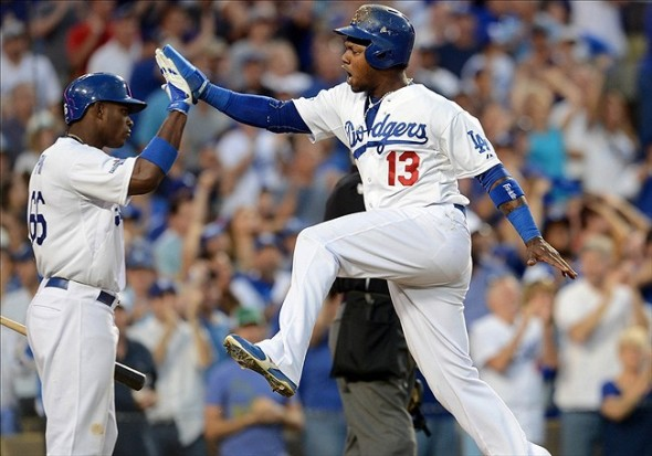 Los Angeles Dodgers shortstop Hanley Ramirez (13) celebrates with right fielder Yasiel Puig (66) after scoring a run in the third inning against the Atlanta Braves in game three of the National League divisional series playoff baseball game at Dodger Stadium. Jayne Kamin-Oncea-USA TODAY Sports