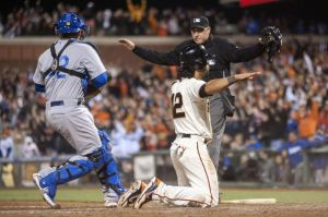 Giants center fielder Angel Pagan (right) signals that he is safe after sliding into home plate during the ninth inning of the game against the Los Angeles Dodgers at AT&T Park. Mandatory Credit: Ed Szczepanski-USA TODAY Sports