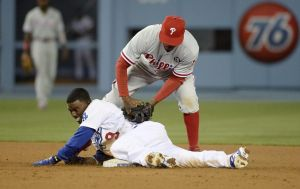 Apr 22, 2014; Los Angeles, CA, USA; Los Angeles Dodgers second baseman Dee Gordon (bottom) slides into second base with a double ahead of the tag by Philadelphia Phillies shortstop Jimmy Rollins (top) in the seventh inning during the game at Dodger Stadium. Mandatory Credit: Richard Mackson-USA TODAY Sports