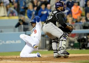 Los Angeles Dodgers second baseman Dee Gordon (9) slides past Colorado Rockies catcher Wilin Rosario (20) to score a run in the third inning of the game at Dodger Stadium.- Jayne Kamin-Oncea-USA TODAY Sports
