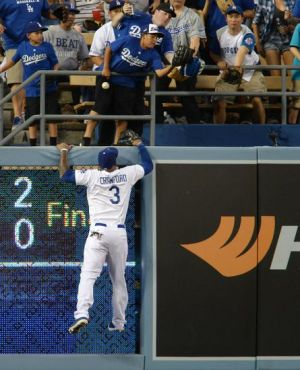 May 14, 2014; Los Angeles, CA, USA; Los Angeles Dodgers left fielder Carl Crawford (3) climbs the wall in pursuit of a 2-run home run ball hit by Miami Marlins third baseman Ed Lucas (59) in the second inning of the game at Dodger Stadium. Mandatory Credit: Jayne Kamin-Oncea-USA TODAY Sports