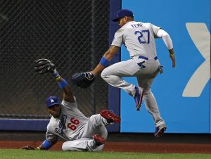 May 22, 2014; New York, NY, USA; Los Angeles Dodgers right fielder Yasiel Puig (66) holds up his glove after making a diving catch on a hit by New York Mets shortstop Wilmer Flores (4) as Dodgers center fielder Matt Kemp (27) jumps over him during the second inning at Citi Field. Mandatory Credit: Adam Hunger-USA TODAY Sports