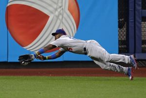May 22, 2014; New York, NY, USA; Los Angeles Dodgers right fielder Yasiel Puig (66) makes a diving catch on a hit by New York Mets shortstop Wilmer Flores (not pictured) during the second inning at Citi Field. Mandatory Credit: Adam Hunger-USA TODAY Sports