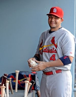 Jun 27, 2014; Los Angeles, CA, USA; St. Louis Cardinals catcher Yadier Molina (4) gets ready in the dugout for the game against the Los Angeles Dodgers at Dodger Stadium. Mandatory Credit: Jayne Kamin-Oncea-USA TODAY Sports