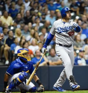 Aug 8, 2014; Milwaukee, WI, USA; Los Angeles Dodgers first baseman Adrian Gonzalez (23) watches after hitting a solo home run in the sixth inning against the Milwaukee Brewers at Miller Park. At left is Milwaukee Brewers catcher Martin Maldonado (12). Mandatory Credit: Benny Sieu-USA TODAY Sports