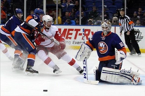 Nov 29, 2013; Uniondale, NY, USA; New York Islanders goalie Kevin Poulin (60) makes a save in front of Detroit Red Wings right wing Mikael Samuelsson (37) and New York Islanders center Casey Cizikas (53) during the third period of a game at Nassau Veterans Memorial Coliseum. The Red Wings defeated the Islanders 5-0. Mandatory Credit: Brad Penner-USA TODAY Sports