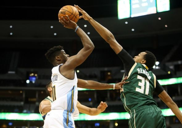 Nov 11, 2015; Denver, CO, USA; Denver Nuggets guard Emmanuel Mudiay (0) has his shot blocked by Milwaukee Bucks forward John Henson (31) during the first half at Pepsi Center. Mandatory Credit: Chris Humphreys-USA TODAY Sports