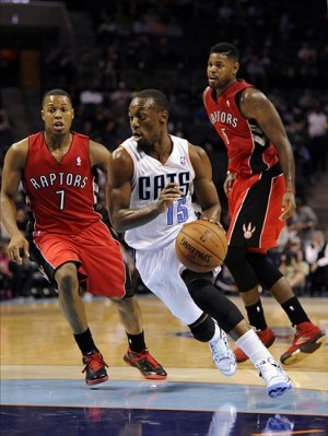 Nov 6, 2013; Charlotte, NC, USA; Charlotte Bobcats guard Kemba Walker (15) drives past Toronto Raptors guard Kyle Lowry (7) and forward Austin Daye (5) during the game at Time Warner Cable Arena. Bobcats win 92-90. Mandatory Credit: Sam Sharpe-USA TODAY Sports