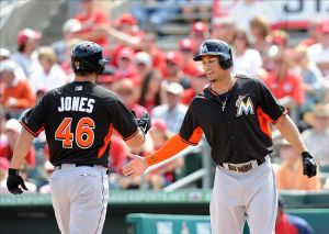 Feb 28, 2014; Jupiter, FL, USA; Miami Marlins right fielder Giancarlo Stanton (right) greets teammate infielder Garrett Jones (left) at home plate after Jones hit a two run homer against the St. Louis Cardinals during a spring training game at Roger Dean Stadium. Mandatory Credit: Steve Mitchell-USA TODAY Sports