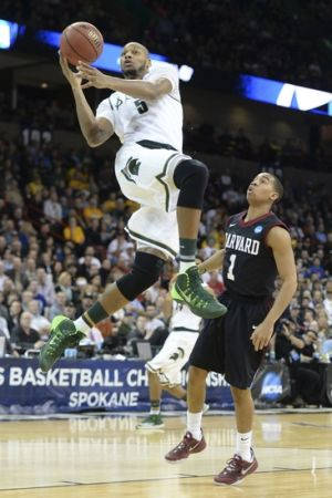Mar 22, 2014; Spokane, WA, USA; Michigan State Spartans forward Adreian Payne (5) shoots against Harvard Crimson guard Siyani Chambers (1) in the first half of a men