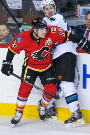Mar 24, 2014; Calgary, Alberta, CAN; Calgary Flames left wing Mike Cammalleri (13) checks into the boards San Jose Sharks center Logan Couture (39) during the first period at Scotiabank Saddledome. Calgary Flames won 2-1 in the shootout. Mandatory Credit: Sergei Belski-USA TODAY Sports