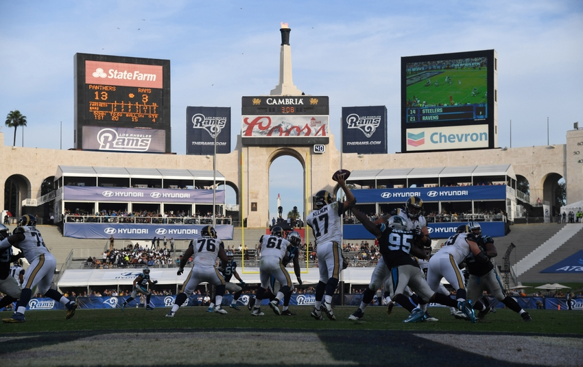 Nov 6, 2016; Los Angeles, CA, USA; General view of a NFL football game at Los Angeles Memorial Coliseum as Los Angeles Rams quarterback Case Keenum (17) throws a pass under pressure from Carolina Panthers defensive end Charles Johnson (95) with the Olympic torch as a backdrop. The Panthers defeated the Rams 13-10. Mandatory Credit: Kirby Lee-USA TODAY Sports