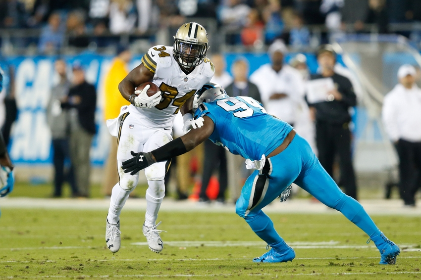 Nov 17, 2016; Charlotte, NC, USA; New Orleans Saints running back Tim Hightower (34) carries the ball as Carolina Panthers defensive end Kony Ealy (94) defends during the fourth quarter at Bank of America Stadium. The Panthers defeated the Saints 23-20. Mandatory Credit: Jeremy Brevard-USA TODAY Sports