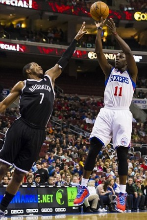 Jan 08, 2013; Philadelphia, PA, USA; Philadelphia 76ers guard Jrue Holiday (11) shoots a jump shot over the defense of Brooklyn Nets guard Joe Johnson (7) during the first quarter at the Wells Fargo Center. Mandatory Credit: Howard Smith-USA TODAY Sports