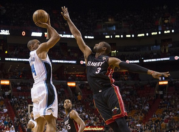 Mar 6, 2013; Miami, FL, USA; Orlando Magic shooting guard Arron Afflalo (4) takes a shot as Miami Heat shooting guard Dwyane Wade (3) defends at the American Airlines Arena. Mandatory Credit: Scott Rovak-USA TODAY Sports