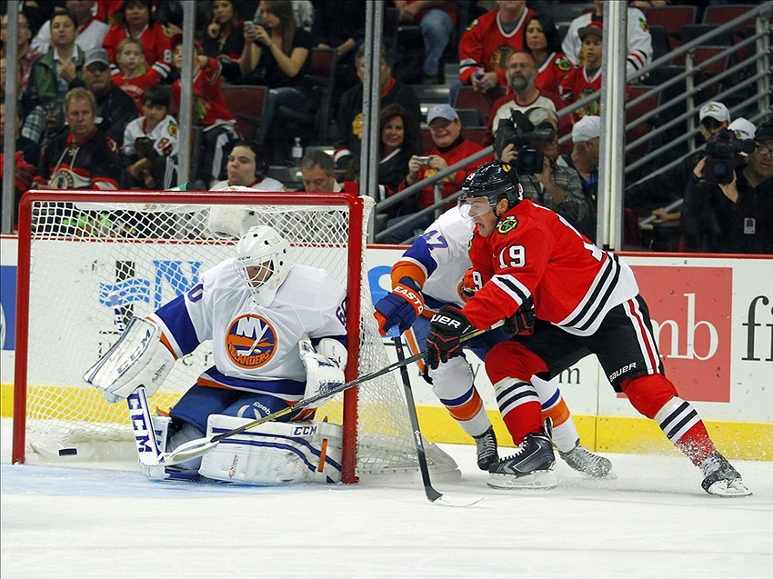 Oct 11, 2013; Chicago, IL, USA; Chicago Blackhawks center Jonathan Toews (19) tries to stuff the puck past New York Islanders goalie Kevin Poulin (60) during the first period at the United Center. Mandatory Credit: Dennis Wierzbicki-USA TODAY Sports