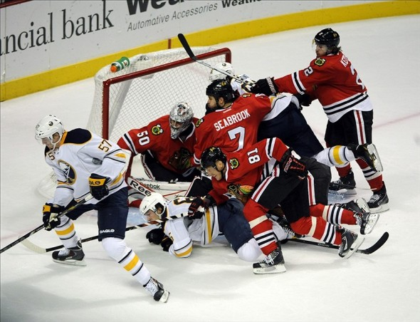 Oct 12, 2013; Chicago, IL, USA; Chicago Blackhawks goalie Corey Crawford (50) along with defenseman Brent Seabrook (7), Chicago right wing Marian Hossa (81) keep Buffalo Sabres defenseman Tyler Myers (57) from shooting during the second period at the United Center. Mandatory Credit: David Banks-USA TODAY Sports