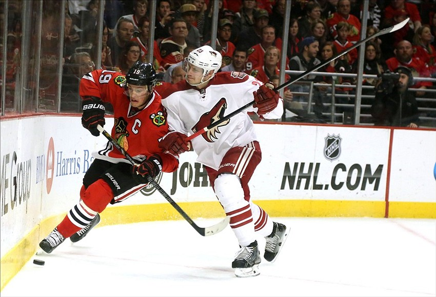 Nov 14, 2013; Chicago, IL, USA; Chicago Blackhawks center Jonathan Toews (19) is checked by Phoenix Coyotes defenseman Oliver Ekman-Larsson (23) during the second period at the United Center. Mandatory Credit: Dennis Wierzbicki-USA TODAY Sports