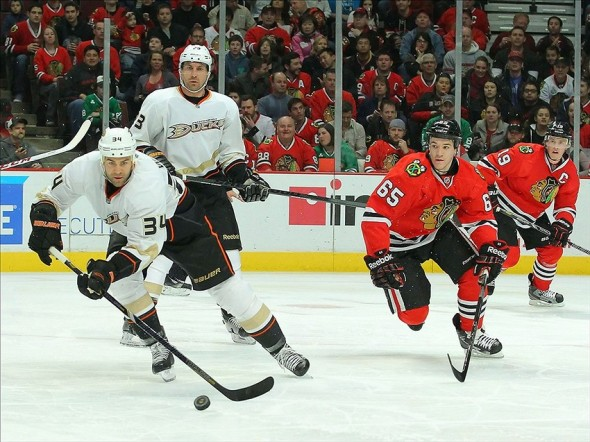 Mar 29, 2013; Chicago, IL, USA; Anaheim Ducks center Daniel Winnik (34) skates past Chicago Blackhawks center Andrew Shaw (65) during the second period at the United Center. Mandatory Credit: Dennis Wierzbicki-USA TODAY Sports