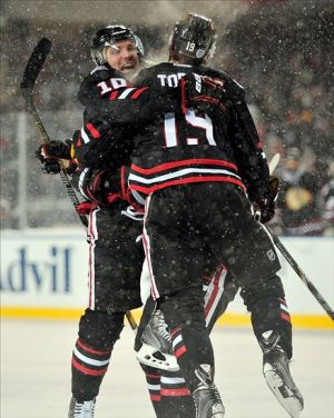 Mar 1, 2014; Chicago, IL, USA; Chicago Blackhawks left wing Patrick Sharp (10) celebrates with center Jonathan Toews (19) after scoring a goal against the Pittsburgh Penguins in the first period in a Stadium Series hockey game at Soldier Field. Mandatory Credit: Rob Grabowski-USA TODAY Sports