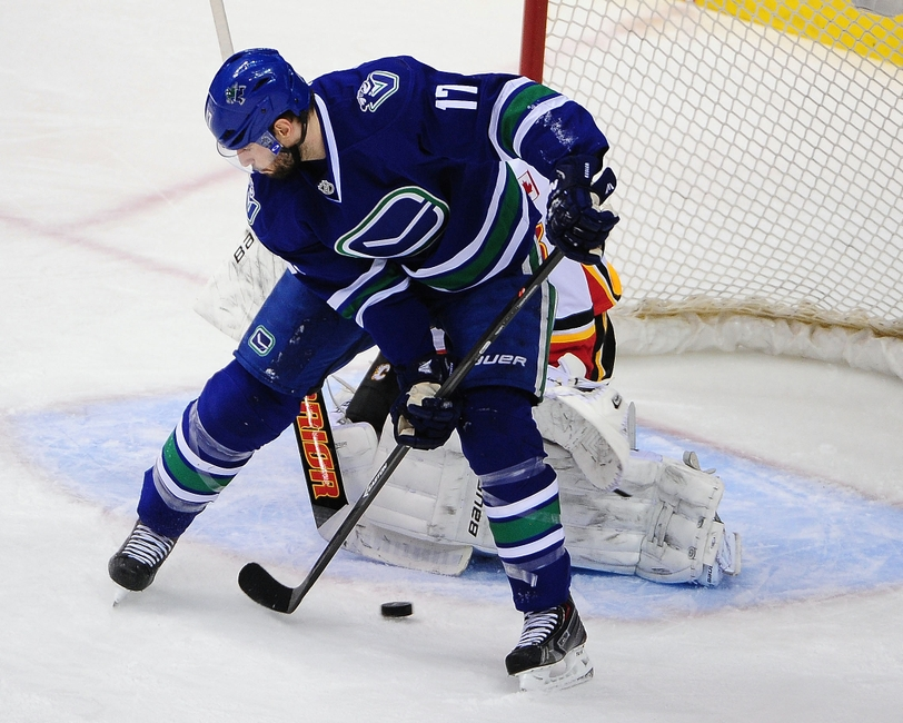 Apr 13, 2014; Vancouver, British Columbia, CAN; Vancouver Canucks forward Ryan Kesler (17) moves the puck in front of Calgary Flames goaltender Karri Ramo (31) during the second period at Rogers Arena. Mandatory Credit: Anne-Marie Sorvin-USA TODAY Sports