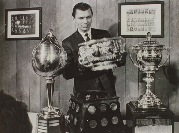 Stan Makita posing with his Hart Trophy, Art Ross Trophy, and Lady Byng Trophy. (Photo courtesy of hfboards.hockeysfuture.com)
