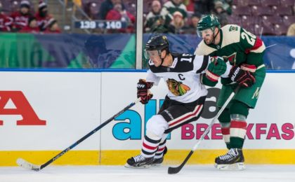 ... Blackhawks forward Jonathan Toews (19) protects the puck from Minnesota  Wild forward Thomas Vanek (26) in the game during a Stadium Series hockey  game ... e19ad3148