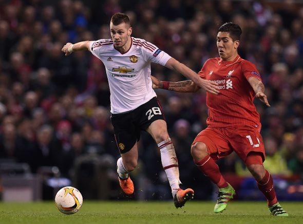 Liverpool's Brazilian midfielder Roberto Firmino (R) vies with Manchester United's French midfielder Morgan Schneiderlin during the UEFA Europa League round of 16, first leg football match between Liverpool and Manchester United at Anfield in Liverpool, northwest England on March 10, 2016. / AFP / PAUL ELLIS (Photo credit should read PAUL ELLIS/AFP/Getty Images)