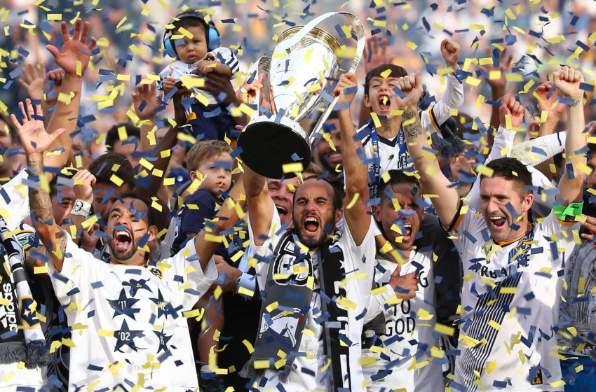 LOS ANGELES, CA - DECEMBER 07: (L-R) Juninho #19, Head Coach Bruce Arena, Landon Donovan #10, Marcelo Sarvas #8 and Robbie Keane #7 of the Los Angeles Galaxy celebrate on the podium with the Philip F. Anschutz Trophy after the Galaxy defeated the New England Revolution 2-1 in the 2014 MLS Cup at StubHub Center on December 7, 2014 in Los Angeles, California. (Photo by Victor Decolongon/Getty Images)